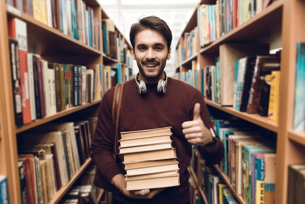 Белый студент в свитер с книгами в междурядье библиотеки. Premium Фотографии