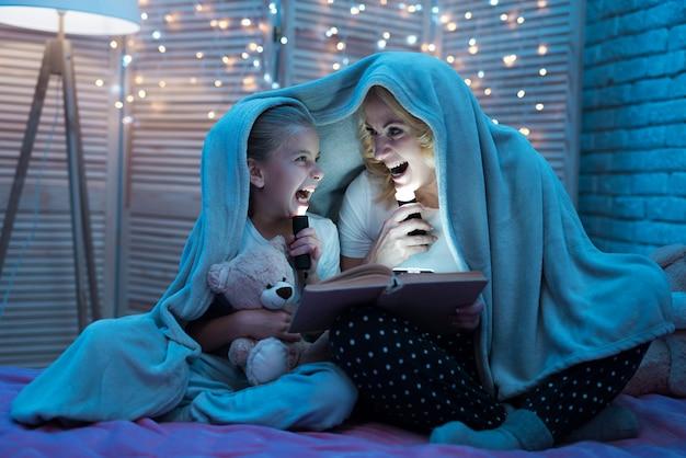 祖母と孫娘の夜に毛布の下に座っています。 Premium写真