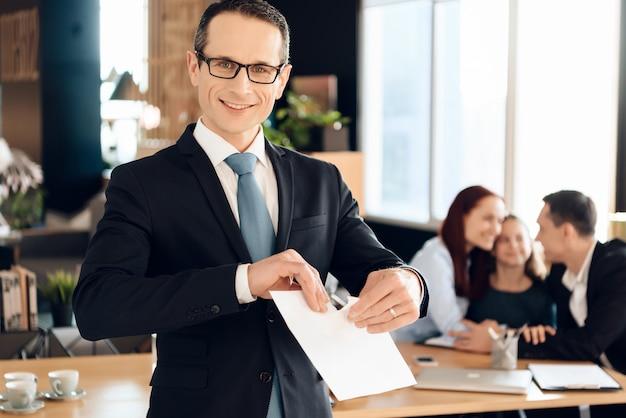スーツのうれしそうな家族弁護士が紙を引き裂きます。 Premium写真