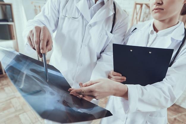 Мужские и женские врачи в белых халатах со стетоскопами Premium Фотографии