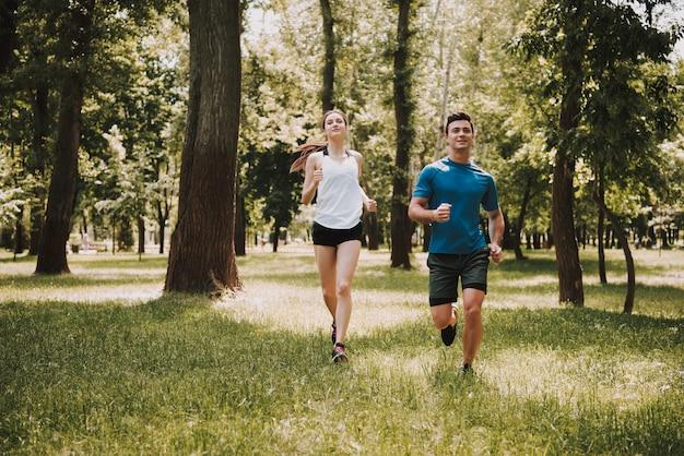 運動選手の愛のカップルは緑豊かな公園で走っています。 Premium写真