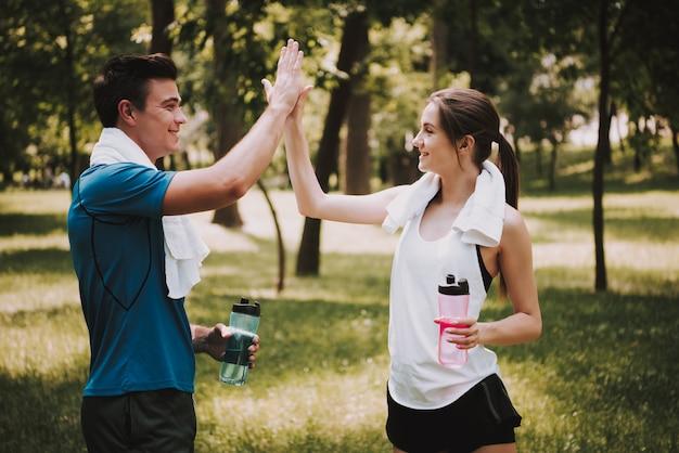 美しい幸せな若いカップルは訓練の後で握手しています Premium写真