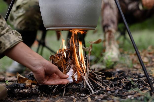 Рука человека поджигает под котелок в лесу. Premium Фотографии