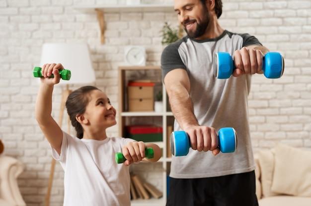 Папа и дочь делают упражнения с гантелями Premium Фотографии