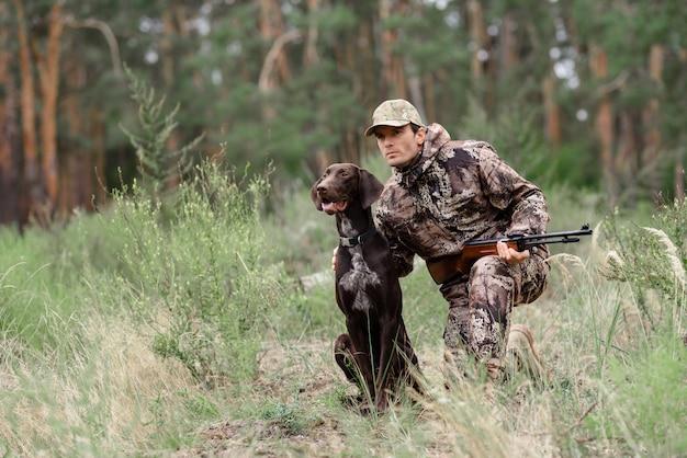 Бдительный охотник и собака в лесу. Premium Фотографии
