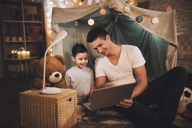 父と息子は自宅で夜にラップトップで映画を見ています。 Premium写真