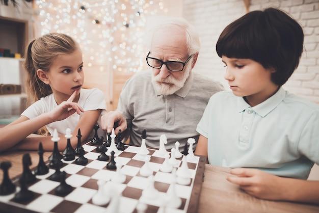 Семья дети играют в шахматы на дому люди думают. Premium Фотографии