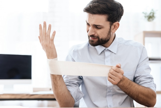 彼の手に痛みを持つ男は白い事務所に座っています。 Premium写真