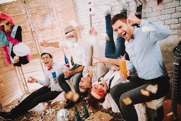 ゲイの男がパーティーでふざけてソファーでポーズします。 Premium写真