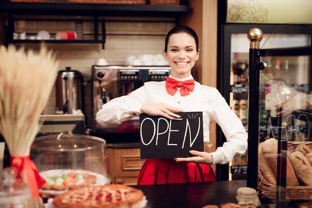 パン屋さんに立っているオープンサインを持つ若い女。 Premium写真