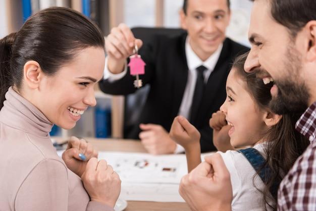 Молодая семья с удовольствием покупает новый дом в офисе риэлтора. Premium Фотографии