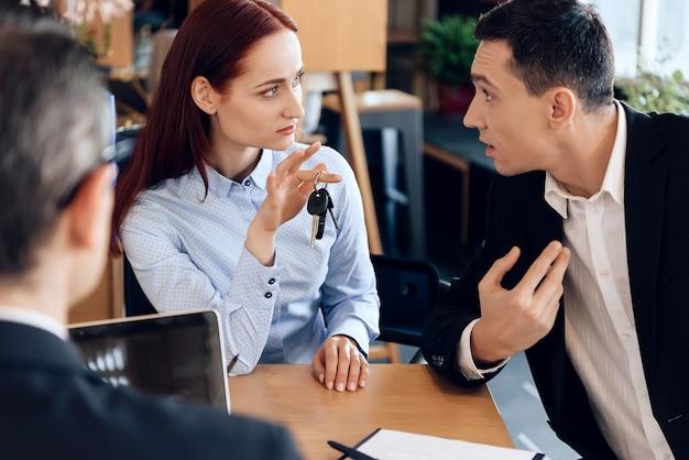 赤い髪の女性は指の鍵を握っています。 Premium写真