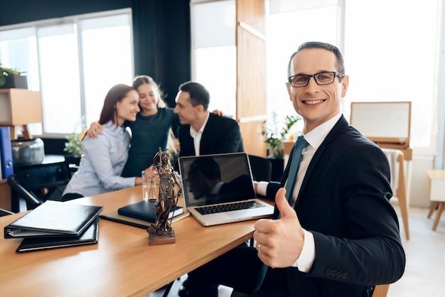 家族の弁護士は、テーブルに座っている間親指を現します。 Premium写真