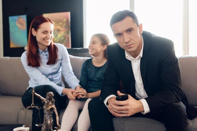 手で電話を持つ欲求不満な父はソファに座っています。 Premium写真