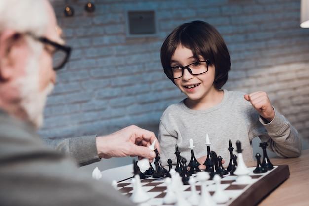 Внук и дедушка вместе играют в шахматы Premium Фотографии