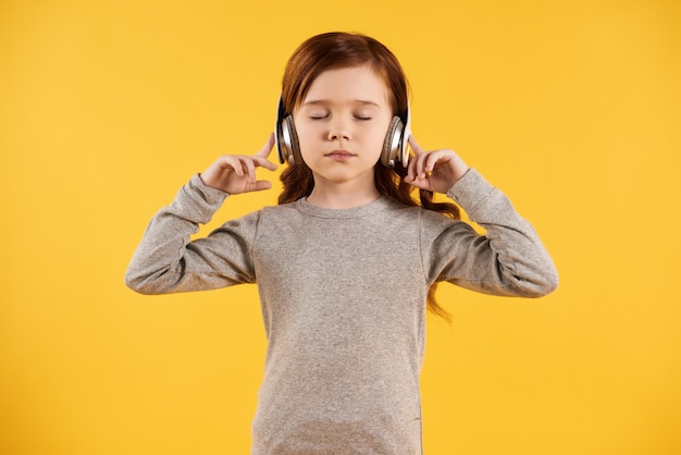 ヘッドフォンで小さな女の子を集中してクラシックを聴きます。 Premium写真