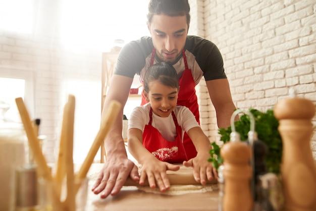 シェフは台所で生地をロールアウトしています。 Premium写真