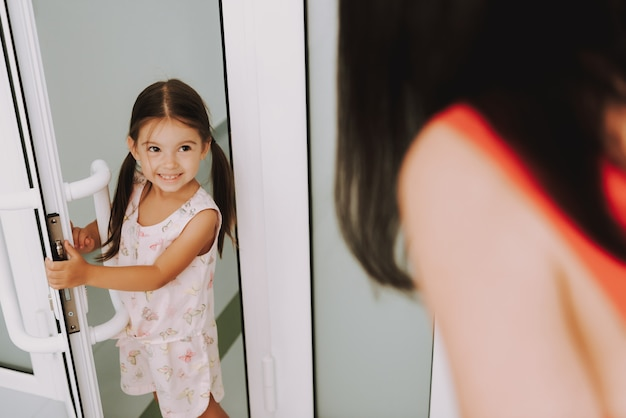 Малыш играет с мамой, открывает двери в детской поликлинике Premium Фотографии