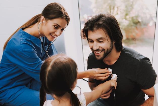 Доктор и ребенок играют слушать человек стетоскоп Premium Фотографии