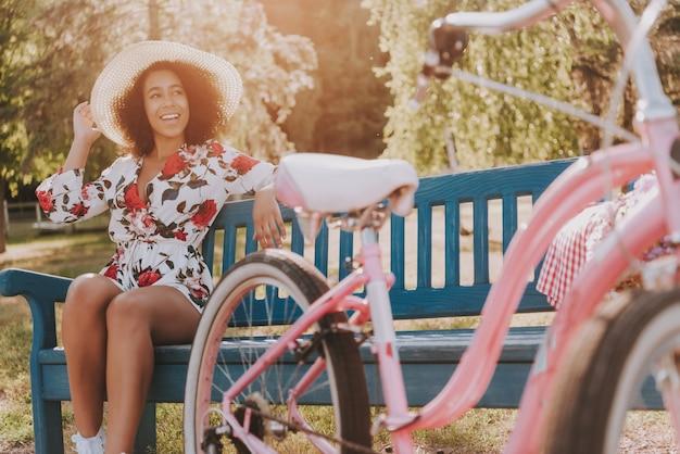 女の子は自転車の横にある公園のベンチに座っています。 Premium写真