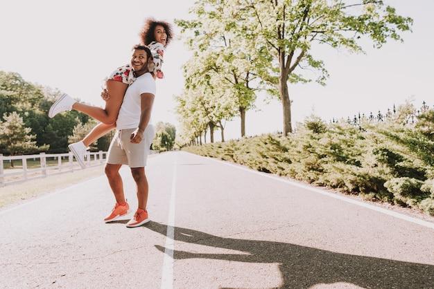 若いラテン男は木の手でガールフレンドを運びます。 Premium写真