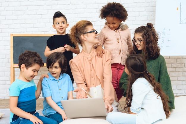 先生は彼女を囲んでいた学童と一緒に座っています。 Premium写真