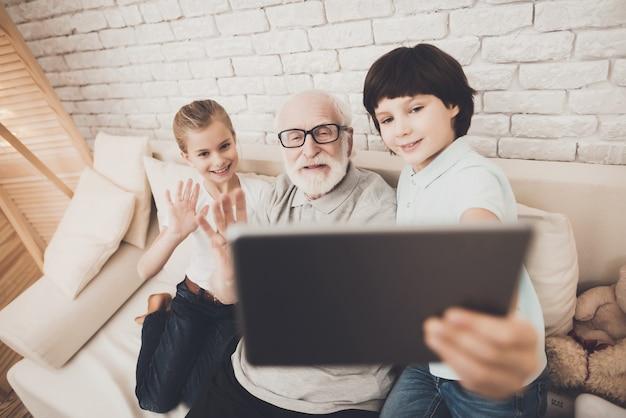 Дети и дедушка сделать видео звонок с планшета. Premium Фотографии