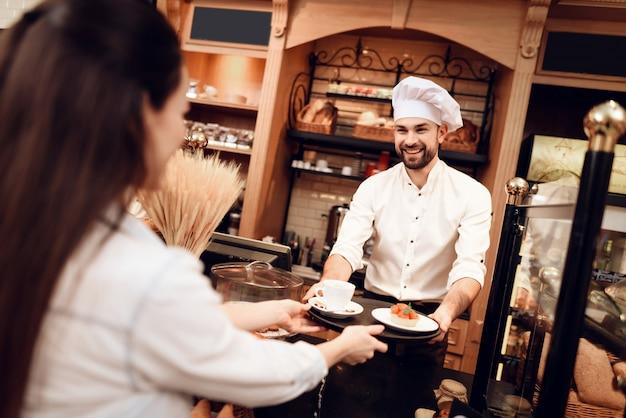 若い男がパン屋で女性にケーキとお茶を売る Premium写真