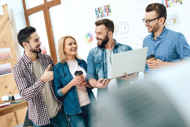 デザイナー建築家のチームはノートパソコンを見ています。 Premium写真