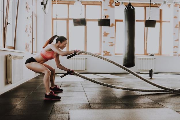 Молодая кавказская дама тренируется с веревками. Premium Фотографии