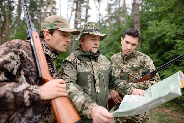 Охотники изучают походную карту определите путь в лесу. Premium Фотографии
