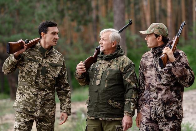 Беззаботные охотники гуляют по сосновому лесу. Premium Фотографии