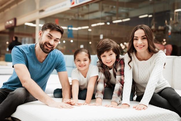 一緒にマットレスを選ぶ若い幸せな家族 Premium写真
