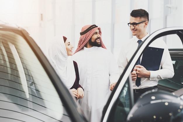 セールスマンはアラブ人と女性に車のクレジットを提供します。 Premium写真