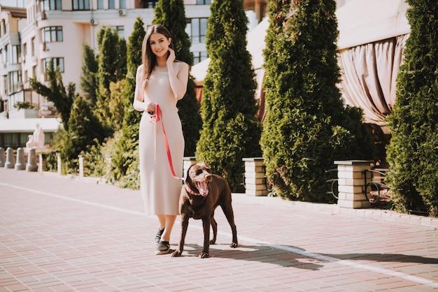 美しい幸せな白人の女の子は彼女の犬と一緒に歩いています。 Premium写真