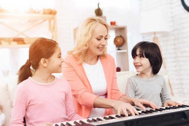 家でピアノを弾くことを教える子供たちとおばあちゃん Premium写真
