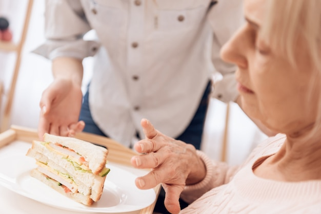 ベッドサンドヴィッチでブドウを食べる病気の女性。 Premium写真