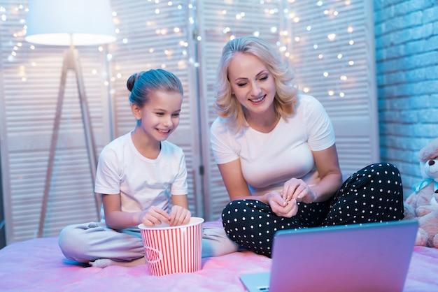 幸せな家族はポップコーンと一緒に映画を見ています。 Premium写真
