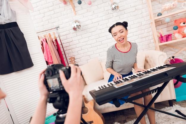 ファッションの女の子がキーボードを弾いて歌う Premium写真
