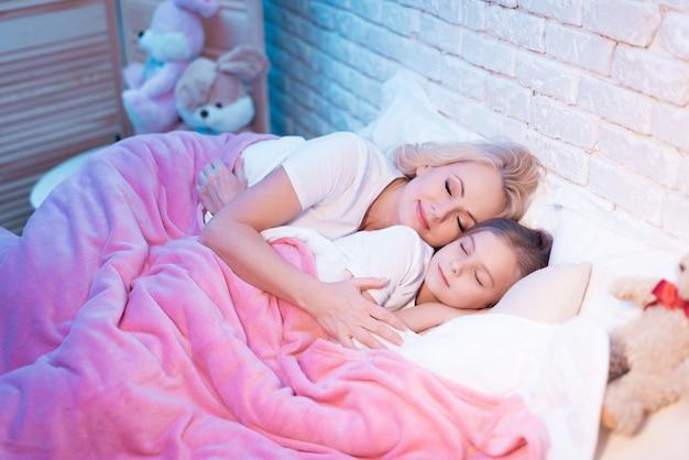 祖母と孫娘は夜ベッドに横になっています。 Premium写真