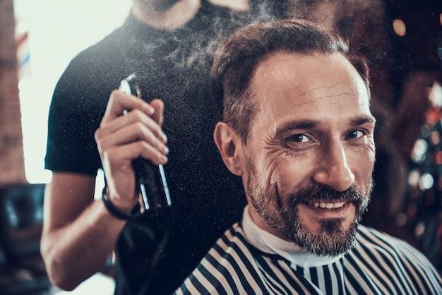 理髪師は、かみそりでハンサムな笑みを浮かべて男を剃ります。 Premium写真