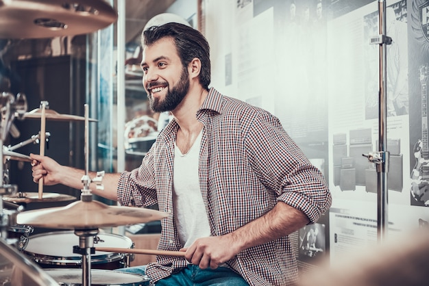 シャツのひげを生やした男はドラムセットを果たしています。 Premium写真