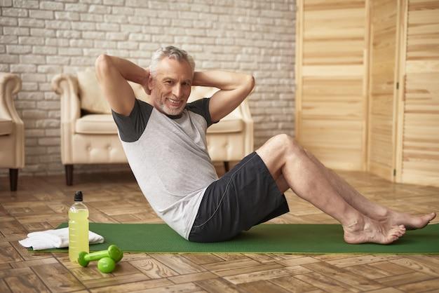 Утренняя пресс-тренировка в домашних условиях пожилой мужчина спорт. Premium Фотографии