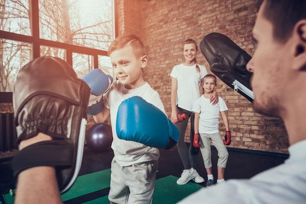 お父さんはジムで手袋で小さなボクサーを訓練します。 Premium写真