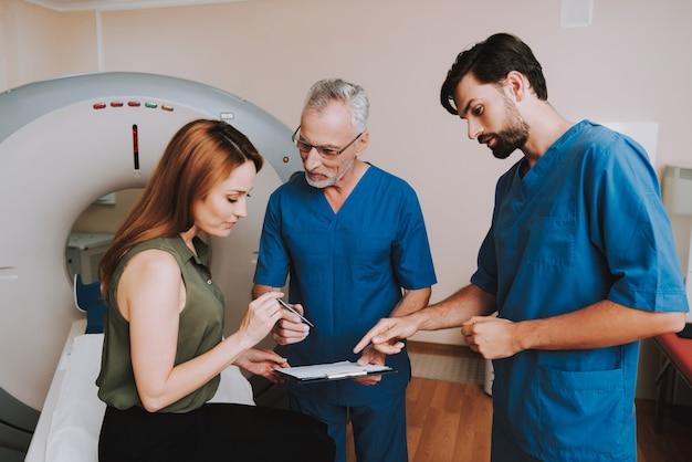 Пациент подписывает бумажный договор на кт. Premium Фотографии