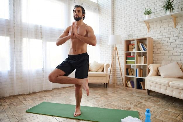 自宅で高度なヨガを練習する裸の胴体を持つスポーツマン。 Premium写真