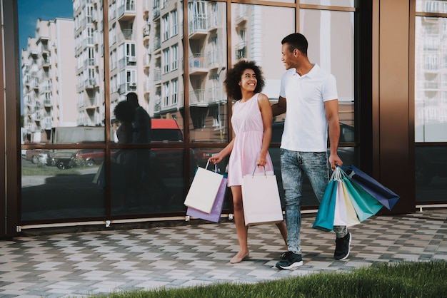 アフリカ系アメリカ人のカップルは買い物袋を持って歩いています Premium写真