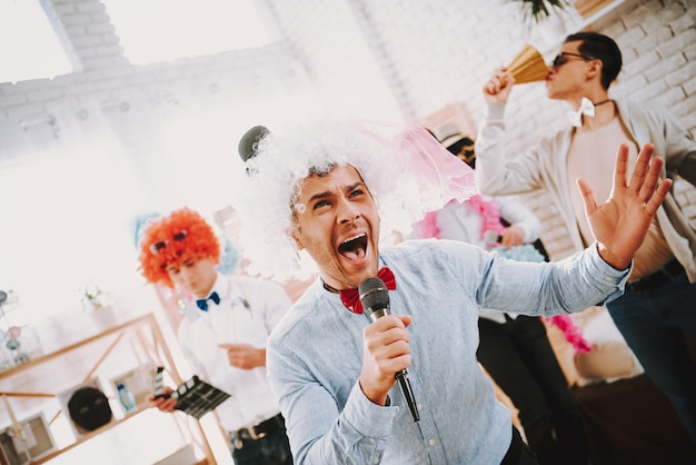 パーティーでカラオケを歌うカラフルな服のゲイの男性。 Premium写真