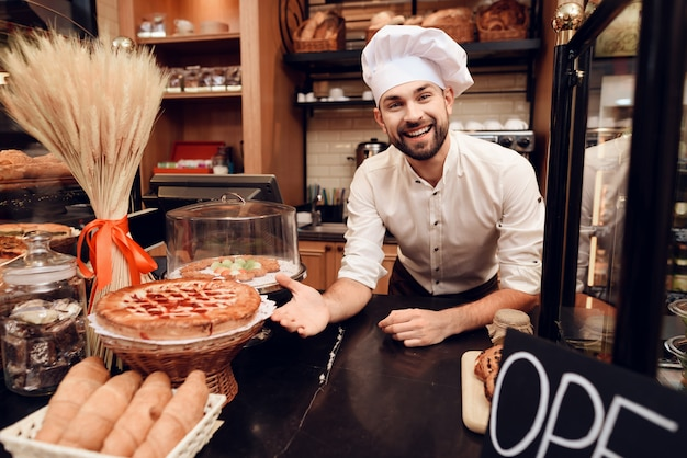 パン屋さんに立っているエプロンでひげを生やした男を笑顔します。 Premium写真