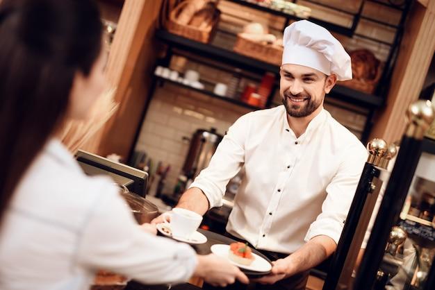 パン屋の女性にケーキやお茶を売る若い男 Premium写真
